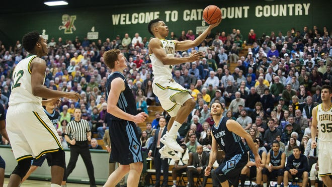 Vermont's Trae Bell-Haynes, right, leaps for a layup during the men's basketball game between the Maine Black Bears and the Vermont Catamounts at Patrick Gym on Feb. 1.