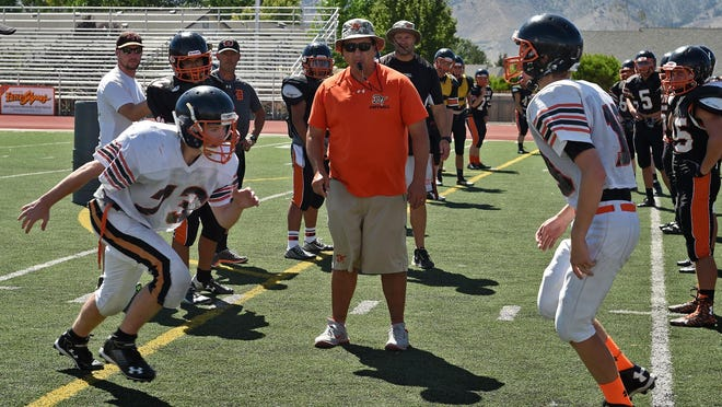 Douglas football coach Ernie Monfiletto, center, watches as his team goes through tackle drills during practice on Aug.