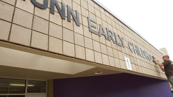 Ben Nikola, manager of Signature Signs, places letters on the new entrance of the John S. Munn Early Childhood Education Center.