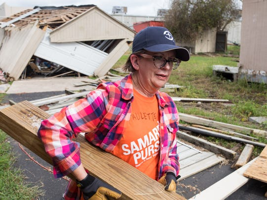 Samaritan's Purse volunteer Paulette Houston of San Antonio hefts a wooden beam while clearing debris from a home on South Arch Street in Aransas Pass on Monday.