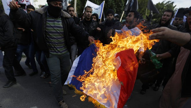 """A Palestinian Salafist burns a French national flag during a protest against the printing of satirical sketches of the Prophet Mohammed by French satirical weekly Charlie Hebdo on January 19, 2015 on their way to the French Cultural Centre in Gaza city. The walls of Gaza's French Cultural Center were painted on January 16 with graffitti in reaction to a cartoon published in the latest issue of Charlie Hebdo showing on its cover the prophet Mohammed holding a """"Je Suis Charlie"""" (I am Charlie) sign under the headline """"All is forgiven""""."""