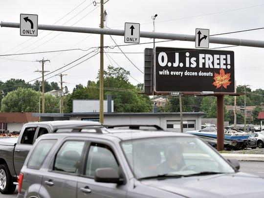 A Maple Donuts billboard advertises free orange juice