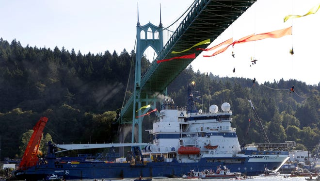 In this July 30, 2015 file photo, the Royal Dutch Shell PLC icebreaker Fennica heads up the Willamette River under protesters hanging from the St. Johns Bridge on its way to Alaska in Portland, Ore.