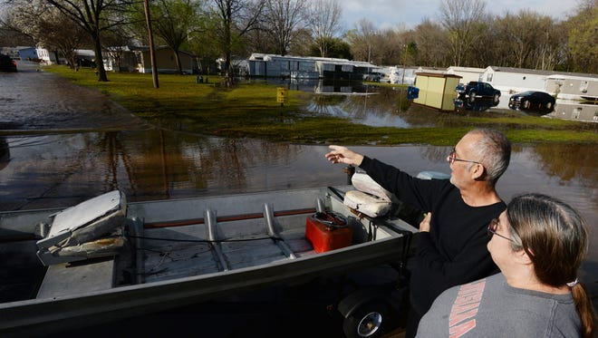 Gary and Lesa Christian waits for help to get their car tow to a more accessible area of Pecan Valley Estates Saturday afternoon. Gary is on dialysis and Lesa worries about the impact the flood will have on his health.
