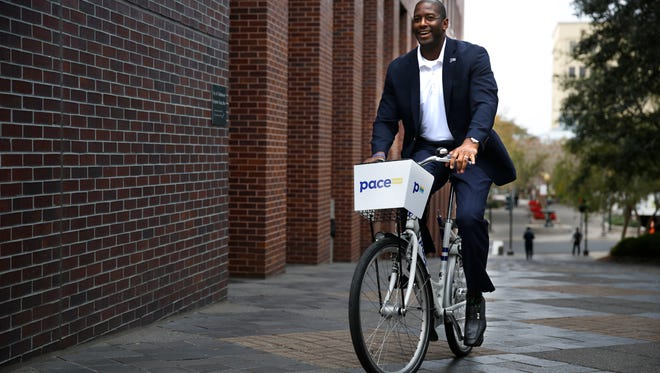 Mayor Andrew Gillum tries out a Pace bike in front of City Hall Monday, one of more than 200 Zagster has deployed in Tallahassee as part of their new bike-sharing program.