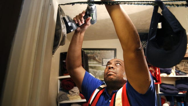 Red Cross volunteer Ralph Campbell installs a smoke detector in Jeffery Darby's Prock Drive house as part of Red Cross fire safety canvassing following a fatal fire last week at a nearby apartment that killed a 5-year-old girl.