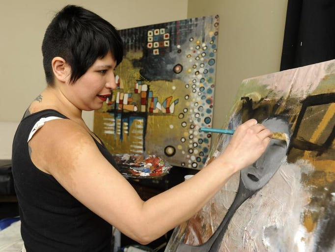 Jennifer White works on a painting at her home in Sioux Falls, S.D., Thursday, Jan. 9, 2014.