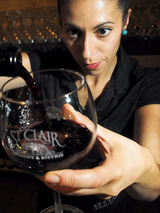 """St. Clair Winery server Fatima Perez, pours a glass of red wine on Monday at the winery. St. Clair has become the only winery in the southwest to achieve """"food grade"""" certification of their production."""