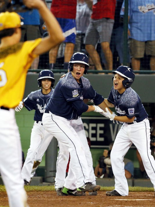 Red Land Little League players Adam Cramer, right, and Cole Wagner, center, celebrate after scoring on a double by Jaden Henline in the team's 9-8 win over Taylors, S.C. Red Land advances to the semifinals of the United States bracket of the Little League World Series, where the team will face Pearland, Texas on Wednesday.