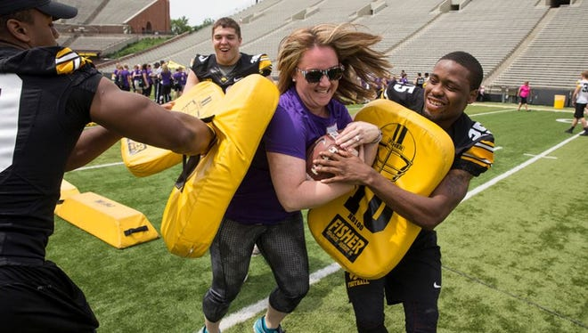 Iowa running back Akrum Wadley, right, helps out a female fan experience a running drill (with light contact) at the 2015 Iowa Ladies Football Academy.