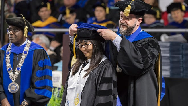 """MTSU doctoral candidate Mo Li, center, receives her academic hood from her adviser, Philip Phillips, English professor and associate dean of the University Honors College, during the university's graduate commencement ceremony in Murphy Center Friday, May 5. Li wrote her Ph.D. dissertation on """"From 'Before the Eye of the World' to 'What I Here Propound is True': Science and Edgar Allan Poe's Building of the Universe."""" University President Sidney A. McPhee is at left."""