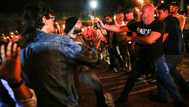 Christopher Cantwell, right, pepper-sprays a counter protester on the University of Virginia campus in Charlottesville on Friday, Aug. 11, 2017. Before the clash the white nationalists marched with torches through the campus until they were met with counterprotest.