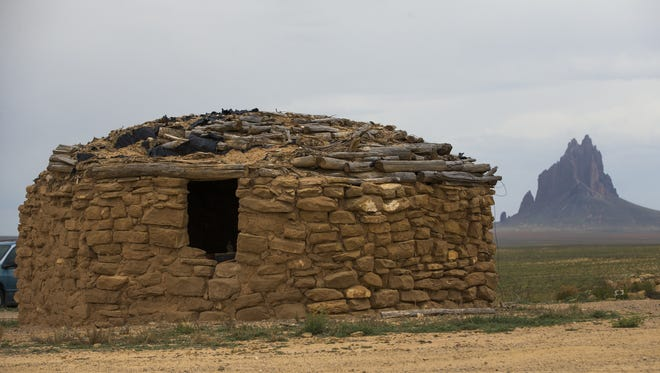 This traditional Navajo hogan was erected within view of the rock formation (background) that gave Shiprock, N.M., its name.