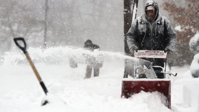 Fields John of Red Bank uses a snow blower to clear someone's  sidewalk and driveway in Red Bank.