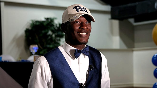 Dunbar High's Shocky Jacques-Louis was all smiles after signing with Pittsburgh during a ceremony at the Dr. Carrie Robinson Event Center on Wednesday.