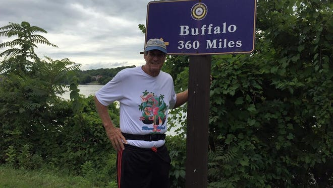Scott Maxwell has his photo taken by a sign as he runs the Erie Canal Marathon Tour, a 366-miler that starts in Albany, New York, and finishes in Buffalo, all along the towpath of the nearly 200-year-old waterway.