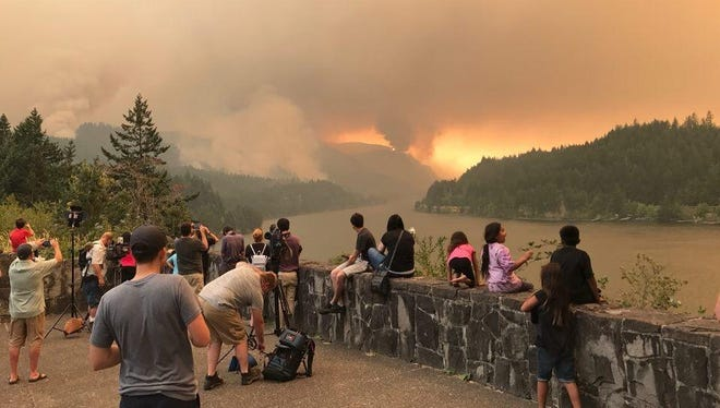 People watch smoke rise from fires in the Columbia River Gorge.