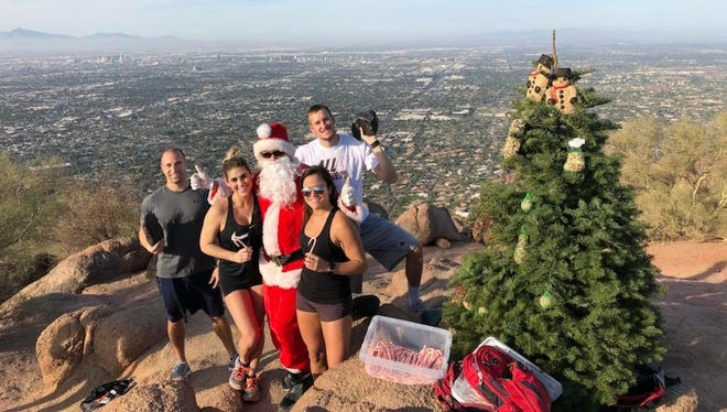 John Cressey, dressed as Santa, poses with a group of hikers on top of Camelback Mountain in December 2017.