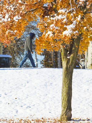 Autumn leaves dusted with snow still cling from a tree as a pedestrian walks north on Jay Street in New Albany Tuesday morning.  Nov. 18, 2014