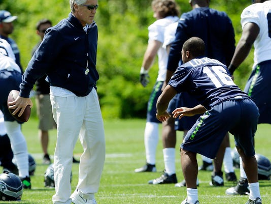Seattle Seahawks head coach Pete Carroll, left, talks with rookie wide receiver Tyler Lockett, right, during NFL football rookie minicamp, Friday, May 8, 2015 in Renton, Wash. (AP Photo/Ted S. Warren)