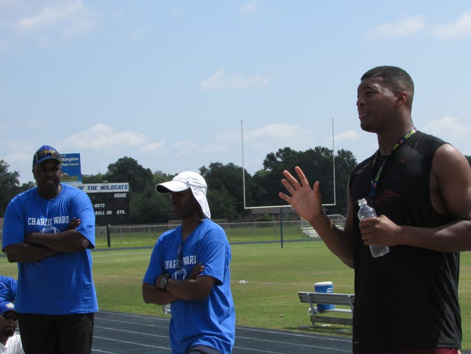 Heisman Trophy-winning Florida State quarterback Jameis Winston, right, addresses the crowd at the Charlie Ward Mentor Leadership Camp, June 14, 2004. Ward, white cap, is the '93 Heisman winner and currently Washington High School football coach.