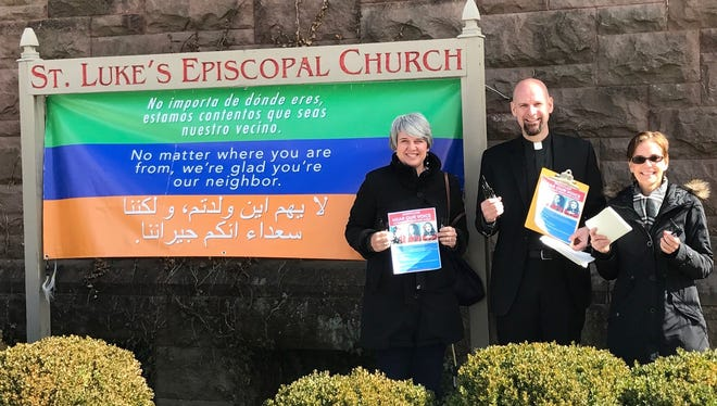Michelle Dice, left, and Angela Suarez, right, two of the organizers behind the Montclair postcard party, join the Rev. John A. Mennell, rector of St. Luke's Episcopal Church in Montclair. The postcard event will be held in the church on Feb. 25.