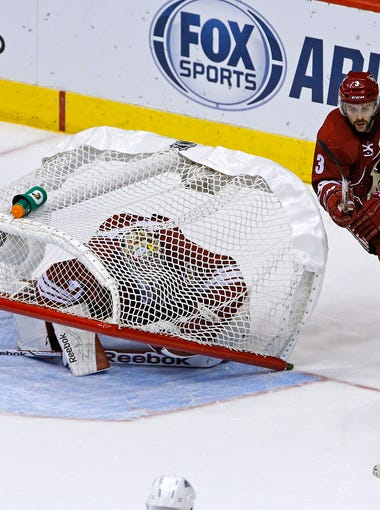 Arizona Coyotes  goalie Mike Smith (41) gets trapped under his own net during the  Colorado Avalanche's  4-3 win during their NHL game Tuesday, Nov. 25, 2014 in Glendale, Ariz.