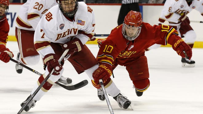 Ferris State defenseman Ryan Lowney (10) dives for the puck as Denver forward Dylan Gambrell (7) controls it during the first period of an NCAA men's hockey West Regional championship in St. Paul, Minn., Sunday, March 27, 2016. (AP Photo/Ann Heisenfelt)