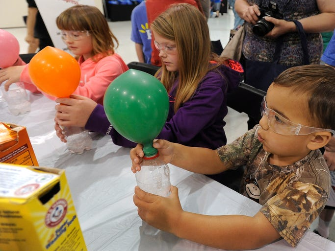 Morgan Damman, Erin Steen and Jackson Hinsch learn about chemical reactions with acids and bases during the 3rd annual Science Festival at Sanford Research Center in Sioux Falls, S.D., Saturday, June 14, 2014.