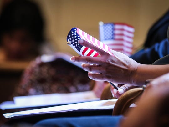 An applicant holds a flag during the naturalization