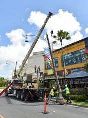 In this May 30 file photo, Polyphase System Inc. employees use a boom truck crane to suspend a streetlight in Tumon as part of the second phase of the San Vitores Streetlight Improvement Project.
