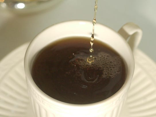 Tea being poured into a serving cup.