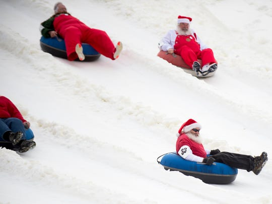 Santas race down the snow tubing park at Ober Gatlinburg on Friday, March 17, 2017.