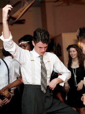 Asheville School's Hank Boyd holds his hat in the air as he dances during Jazz Night at On Broadway March 1, 2017. The school's seniors have been studying American history and literature of the 1920s in their humanities classes. The annual jazz night allows the seniors to bring their studies to life through dance and music of the era.