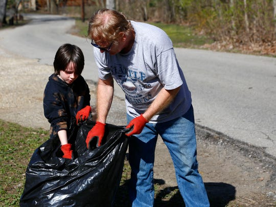 Vince Owens, helps his nephew, Lucian Thull, 8, with cleaning up North Lake Park on Saturday.
