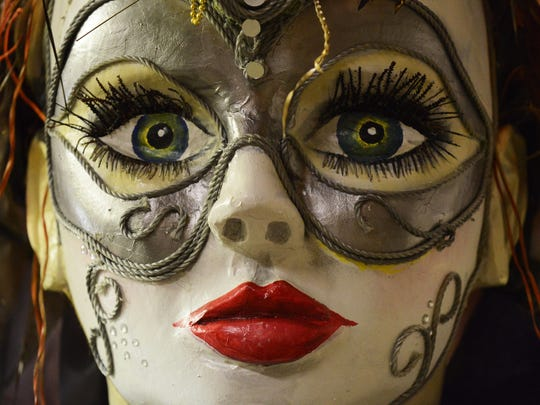 The masked face of a ship-shaped parade float's figurehead looks out in the Krewe of Janus headquarters .