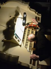 """Organist Jay Spencer checks out the Renaissance Theatre's Wurlitzer organ while still in the bowls of the pit before the start of the annual Christmas With The Mighty Wurlitzer in 2013. Spencer will play the organ to accompany """"Phantom of the Opera"""" Friday."""