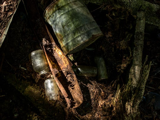 """Glass bottles and scrap metal are seen on """"Glass Hill"""" Thursday, August 4, 2016 near the Black River and Hewitt Road in Grant Township."""