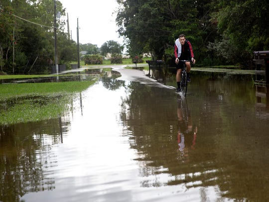 A bicyclist rides down Bottlebrush Lane which experienced flooding caused by heavy rains associated with Tropical Storm Emily on Tuesday, Aug. 1, 2017.