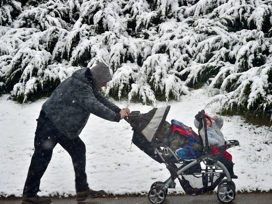 Someone pushes a stroller during snowfall on Friday
