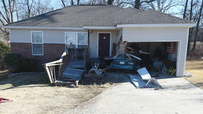 A mangled Mustang can be seen half in the crushed garage of a Gassville home Monday after Ronald Aaron Love allegedly rammed the car and the home several times.