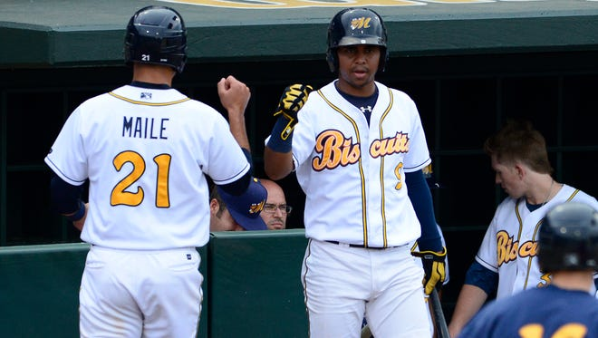 Montgomery Biscuits' Luke Maile (21) is congratulated on scoring by Hector Guevara (9) against the Mobile BayBears at Riverwalk Stadium in Montgomery, Ala. on Sunday June 22, 2014.