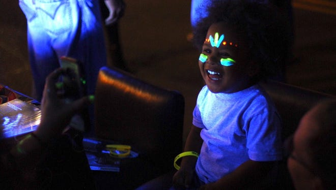 Zeven Schumacher, 2, of Binghamton, smiles after getting his face painted at the Slava's Zombie Circus tent during the LUMA projection arts festival in downtown Binghamton in 2016.