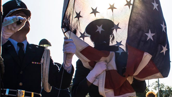 An Angelo State University ROTC Detachment 847 cadet is silhouetted behind the American flag during a flag retreat ceremony at ASU in November 2014.