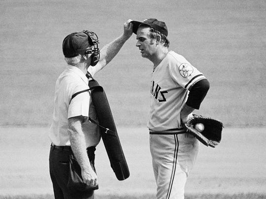 In this Sept. 3, 1973 file photo, home plate umpire John Flaherty checks Cleveland Indians' pitcher Gaylord Perry's cap, at the request of Milwaukee Brewers manager Del Crandall during a game in Milwaukee. Well after the end of his Hall of Fame career, Perry could still joke about his infamous spitball, but in 1982, the Seattle star was ejected for allegedly throwing the pitch against the Boston Red Sox.