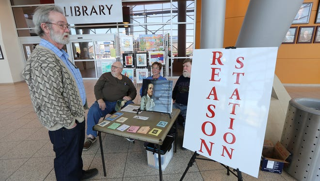 Pete McManus, 71, stands while he waits his turn to man the reason station while Douglas Marshall, 69, sits in the back along with Lynne Lundgren, 64, and George Haskin, 72, while they volunteer to sit at the Warren City Hall on Tuesday, April 28, 2015.