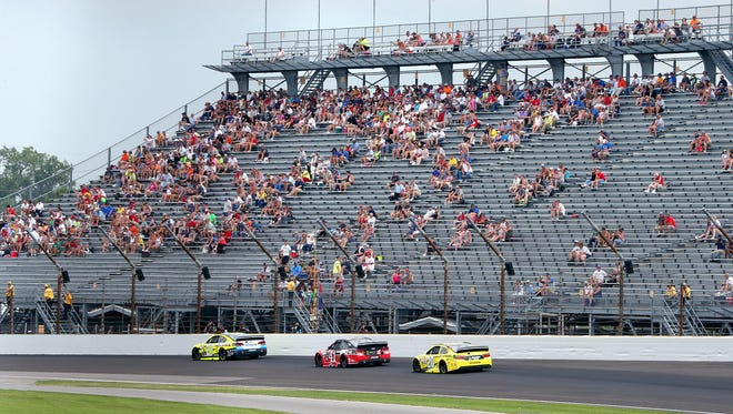 Fans watch the action on the track as the cars race through the first turn during the 22nd Jeff Kyle 400 at the Brickyard Sunday, July 26, 2015, afternoon at the Indianapolis Motor Speedway.