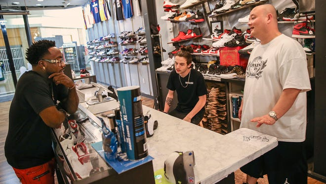 Grails Inc. owner Paul Zigrang and employee Hadyn Mayes help a customer at the Washington Square Mall store. Grails Inc. specializes in hot-selling, collectible new and used sneakers.