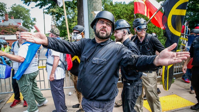 Matt Heimbach, a white nationalist who calls Indiana home, yells at counterprotesters as he leaves Emancipation Park alongside his Traditionalist Worker Party members in Charlottesville, Va., on Saturday, August 12, 2017. Multiple white nationalist groups marched to McIntire Park after the 'Unite the Right' rally was declared an unlawful assembly.