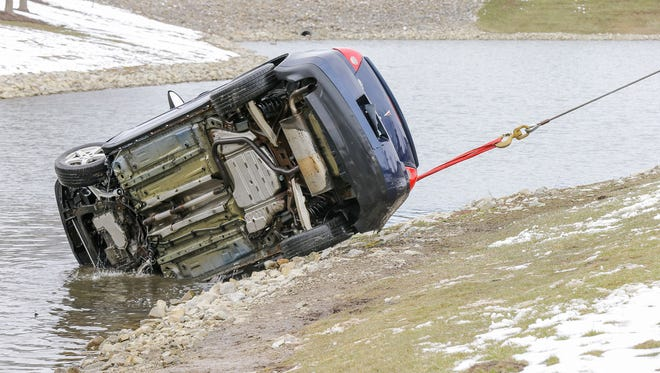 A car is pulled from a retention pond at an apartment complex in Indianapolis on Monday, March 26, 2018. The car rolled into the water Sunday, March 25, 2018, with a 3-year-old girl inside. The girl was rescued, but her father died trying to save her.